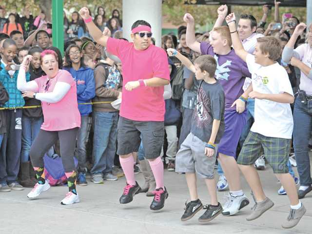 Campus supervisor Angela Sharady, left, and English teacher Rob Isquierdo Jr., second left, dance with students during a flash mob event on Friday.