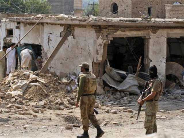 Pakistani men, left, check the damage caused by a car bomb explosion, while army soldiers gather at the site in the Pakistani town of Darra Adam Khel in the troubled Khyber Pakhtunkhwa province bordering Afghanistan, Saturday, Oct. 13, 2012.