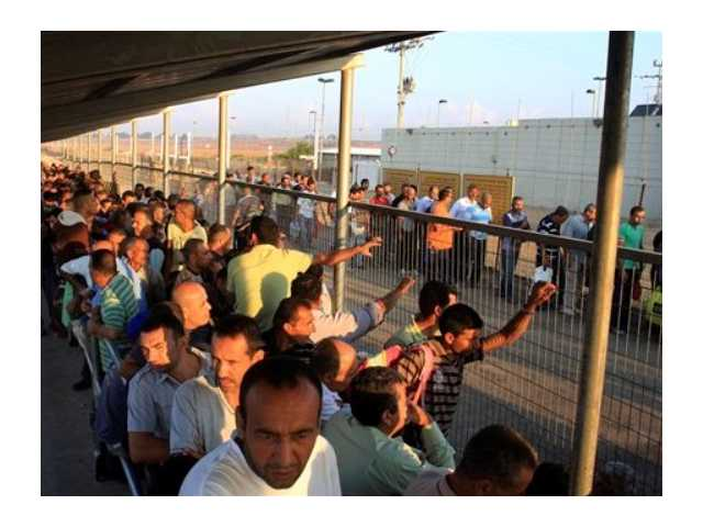 In this Tuesday, Oct. 9 photo, Palestinian workers wait to cross to Israel at the Qalqiliya checkpoint. In response to an economic crisis gripping the West Bank, Israel has suddenly increased the number of permits for Palestinians to work inside Israel.