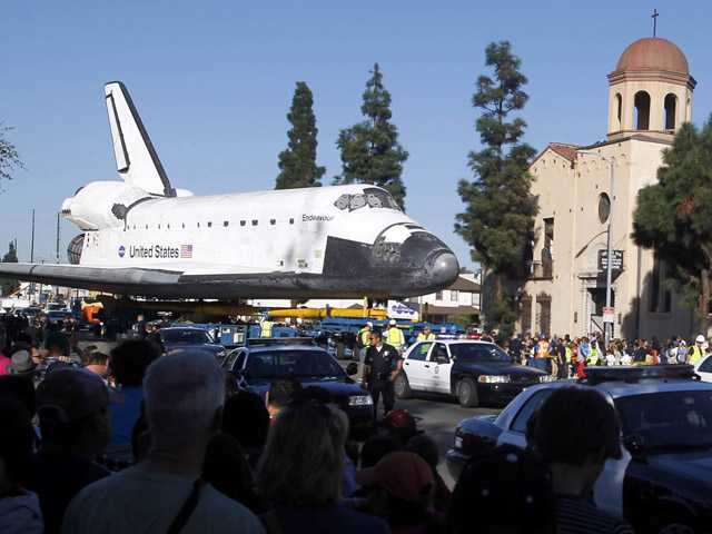 Spectators watch the space shuttle Endeavour slowly move down Martin Luther King Blvd. in Los Angeles on Sunday.