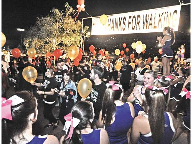 The Valencia High School cheerleaders, right, cheer on the hundreds of walkers as they participate in the Light the Night Walk to benefit leukemia and lymphoma research held at Bridgeport Park in Valencia on Saturday.