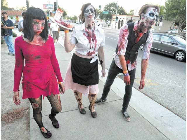 Zombies from left, Jessica Arias, Gina Glenn and Justin Glenn join a small group of ghouls during the Zombie walk along Newhall Avenue in Newhall.