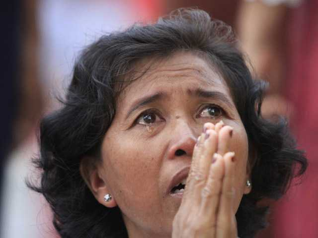 A Cambodian woman prays in tears in front of the main gate of the Royal Palace in Phnom Penh, Cambodia, to mourn the death of former King Norodom Sihanouk