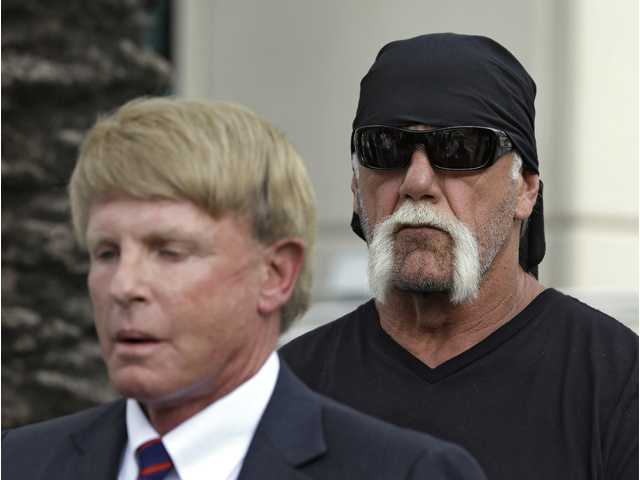 Reality TV star and former pro wrestler Hulk Hogan looks on as his attorney David Houston speaks during a news conference on Monday.
