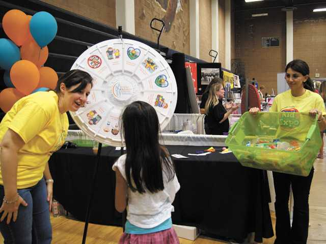 Child & Family Center volunteer Susan Wood, left, helps a young girl with a spin of the wheel at Sunday's Kid Expo 2012 put on by the Child & Family Center at Golden Valley High School.