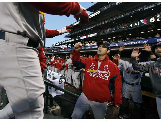 St. Louis Cardinals manager Mike Matheny congratulates Carlos Beltran, foreground left, as he returns during Sunday's game in San Francisco.