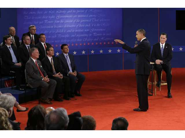 President Barack Obama answers a question as Mitt Romney listens during the second presidential debate at Hofstra University.