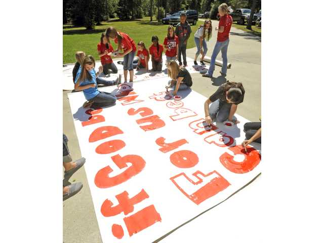 High School cheerleaders and other children work on a sign in Kountze, Texas. The district told the cheerleaders to stop using Bible verses at football games.