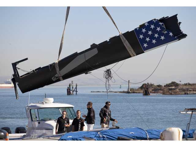 Part of a wing section of the capsized Oracle Racing boat is lifted out onto a pier at the team's headquarters in San Francisco, Wednesday.