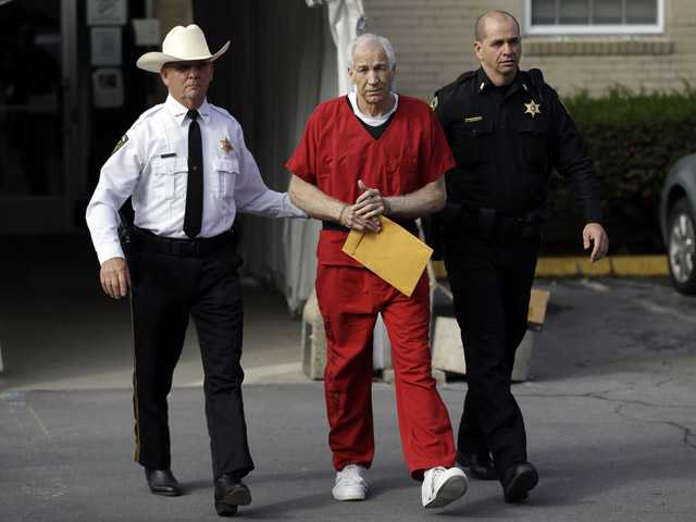 Jerry Sandusky, center, is taken by Centre County Sheriff Denny Nau, left, and a deputy in Bellefonte, Pa., Oct. 9.