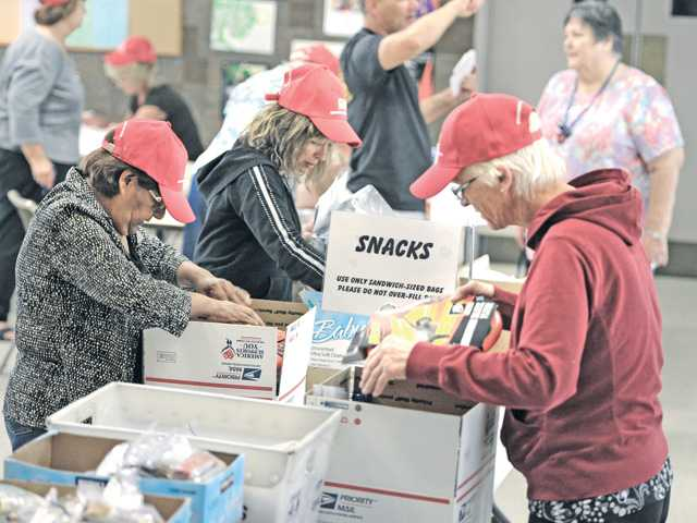 A group of volunteers fill boxes with snacks, toiletries, magazines and DVDs to be sent to troops overseas from Christian Lutheran Church in Valencia. The church filled it's 6,000th box on Tuesday night. For the story, see A6.
