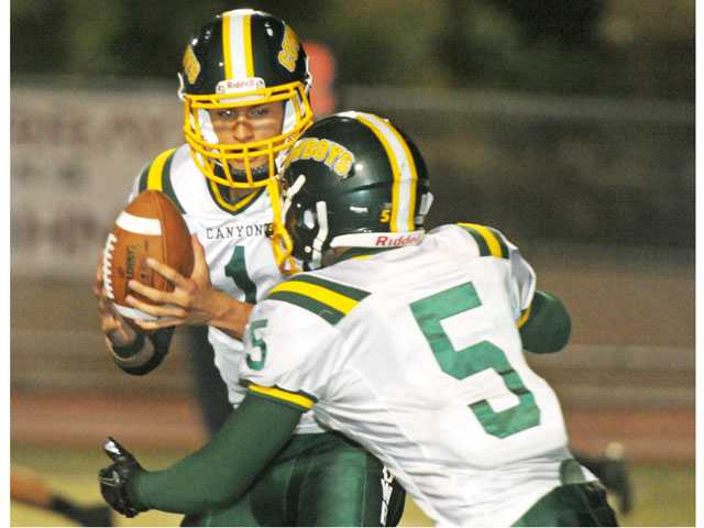 Canyon quarterback Cade Apsay, left, hands off to running back Daniel Castro on Oct. 12 at College of the Canyons.