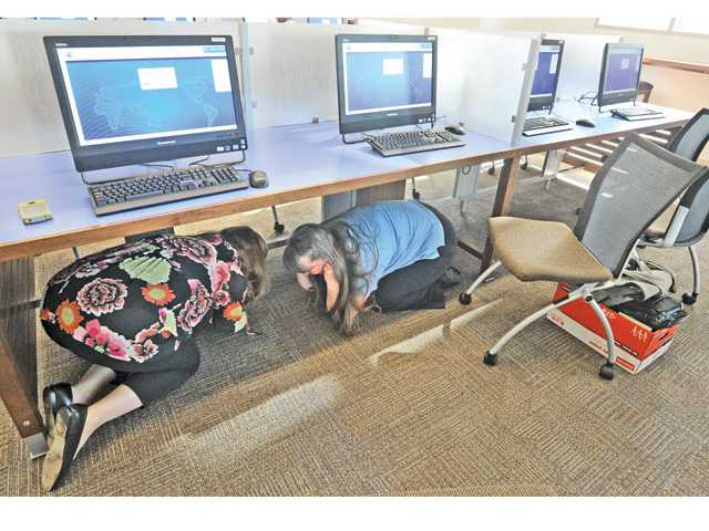 Santa Clarita Public Library Volunteer Coordinators Stacy Schlesinger, left, and Kathi Lund duck under a desk in the Newhall Library during the California ShakeOut event on Thursday morning.