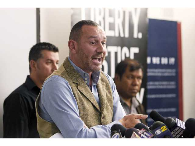 Lead plaintiff Duncan Roy announces a federal lawsuit by the American Civil Liberties Union on behalf of arrestees who say they were denied bail because they had federal immigration holds, in Los Angeles on Friday.