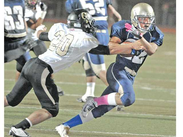 West Ranch's Zahr Lyttle (22), right, looks for running room on Friday night at Valencia High.