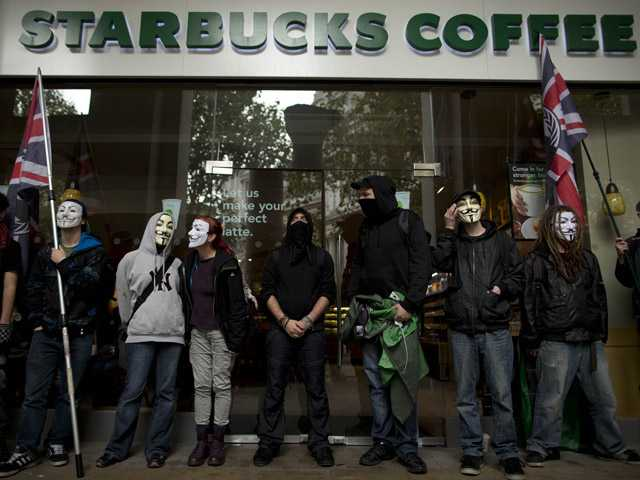 Demonstrators stand outside a Starbucks near St Paul's Cathedral before an anti-austerity protest march through London, Saturday.