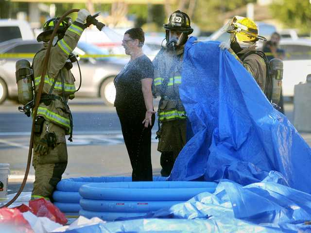 In this photo taken Oct. 19, a Chase Bank employee is decontaminated outside a branch in Modesto.