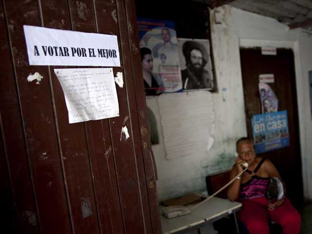 "A woman answers the phone at a boxing gym where a sign hangs on the door that reads in Spanish ""A vote for the best"" in Old Havana, Cuba, Saturday."