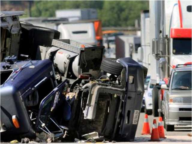 Officials investigate a fatal crash involving a big rig on the eastbound Pomona (60) Freeway in Diamond Bar, Calif., Friday, Oct. 19, 2012. One person died at the scene and three others were injured, according to officials. (AP Photo/Los Angeles Times, Irfan Khan)