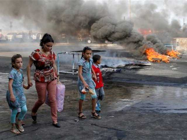 A family walks past flaming tires used as a roadblock to protest the death of Brig. Gen. Wissam al-Hassan, head of the intelligence division of Lebanon's domestic security forces in a car bomb attack targeting his convoy, in the southern port city of Sidon, Lebanon, Saturday, Oct. 20, 2012.