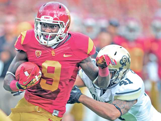 USC wide receiver Marqise Lee (9) runs the ball as Colorado defensive back Terrel Smith trails on Saturday at Los Angeles Memorial Coliseum. USC won 50-6.
