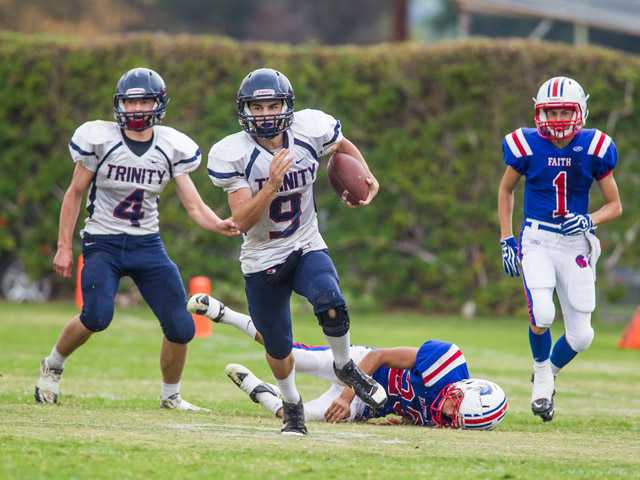 Trinity QB Dakota Prochnow (9) runs for daylight after leaving Faith Baptist's Matthew Carter (1) behind.