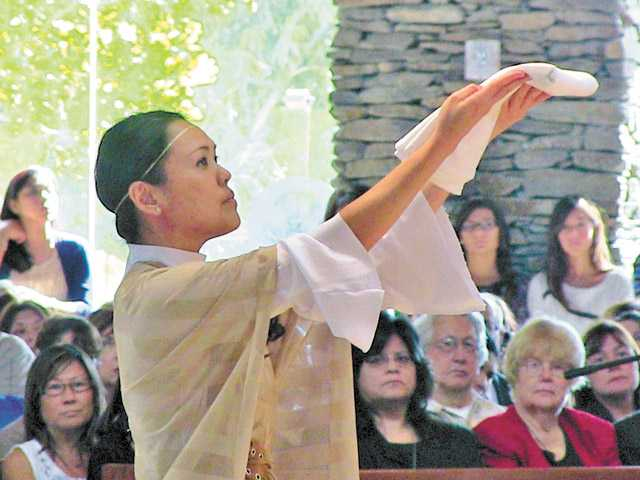 Liturgical dancer Toyo Yano walks to the altar during the canonization Mass at St. Kateri's Catholic Church in Santa Clarita on Sunday.