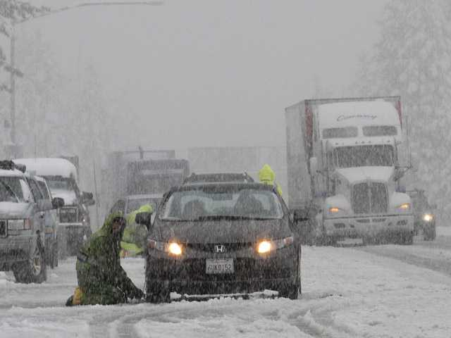 Chain installers work as snow falls on eastbound Interstate 80 near Nyack on Monday.