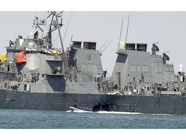 Investigators in a speed boat examine the hull of the USS Cole at the Yemeni port of Aden, after a powerful explosion ripped a hole in the destroyer.