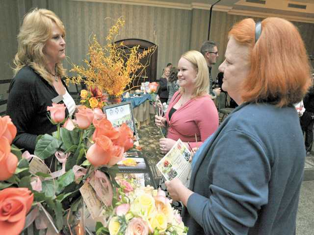 From left, Charmaine Wojciechowski of Charmaine's Bouquet Canyon Florist discusses her services with bride-to-be Kim Elwell, of Valencia, and her mother Glynis Elwell at The White Stage on Oct. 11.