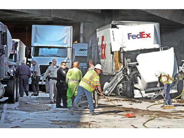 Workers spread sand on spilled diesel fuel at the scene of a crash involving multiple big-rig trucks at the southbound Interstate 5 truck tunnel in the Newhall Pass that occurred in the early morning hours on Tuesday.