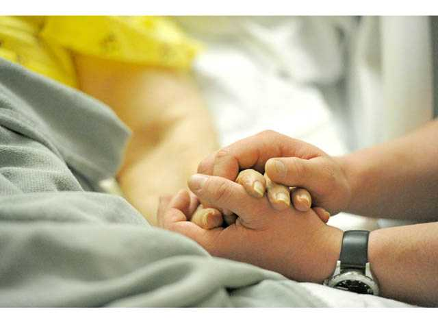 Axen, right, holds patient Margaret Genova's hand as he sings for her.