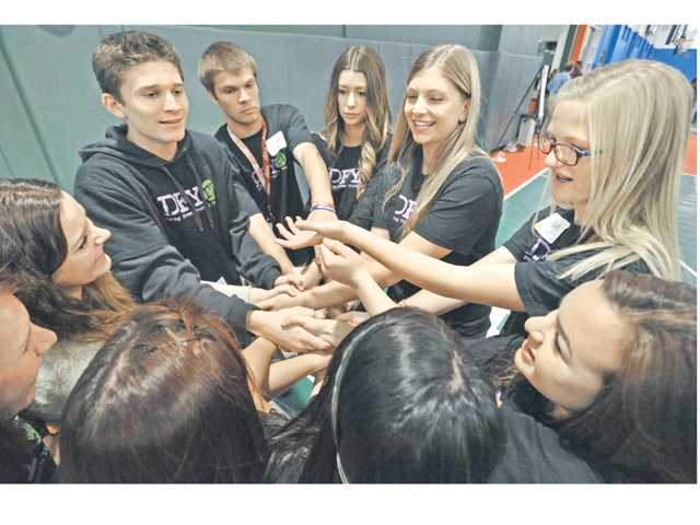 "A group of high school students joins hands to execute a ""human knot"" exercise during team-building activities at the DFYiT student summit Wednesday. Signal photo by Dan Watson"