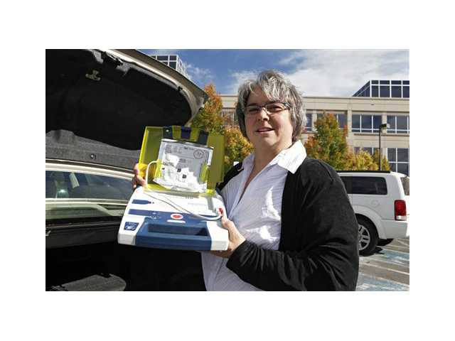 Mary Tappe holds up the defibrillator that she keeps in the trunk of her automobile during a work break on Tuesday at the Western Union headquarters in Englewood, Colo.