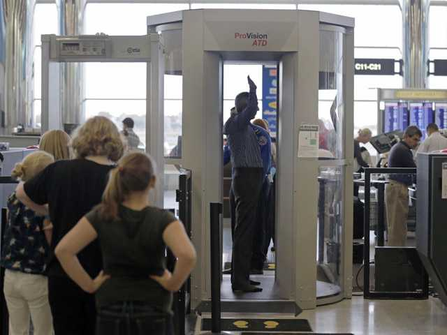 In this Wednesday photo, passengers are scanned at a Terminal C security checkpoint at Logan Airport in Boston using a millimeter wave body scanner.