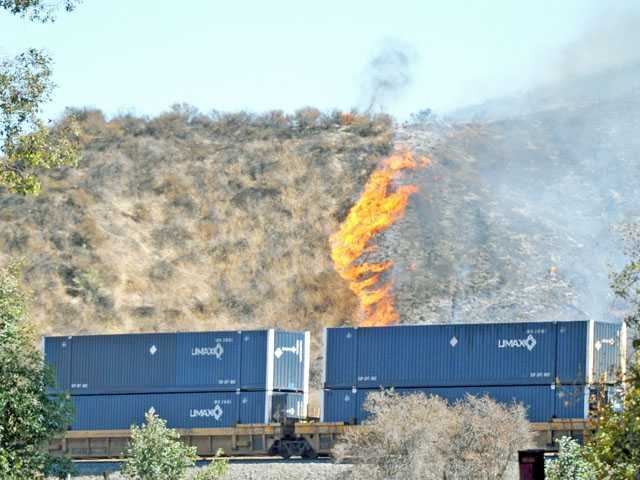 A freight train makes its way past a brush fire burning in hills along Soledad Canyon Road near the Centre Pointe district of Santa Clarita on Thursday.