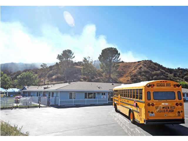 Children are evacuated from the Creative Years Preschool as smoke emerges from a brush fire near the Centre Pointe district of Santa Clarita on Thursday.