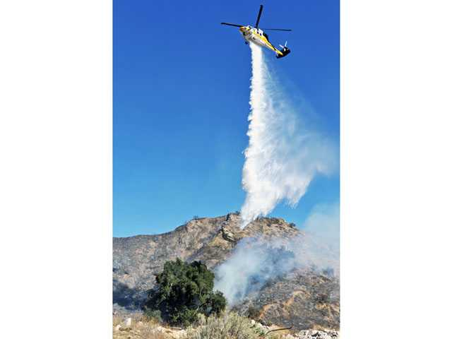 A helicopter drops water after a fire consumes brush in the hills along Soledad Canyon Road near the Centre Pointe district of Santa Clarita on Thursday.
