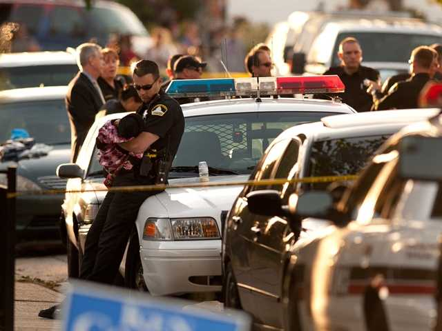 Rancho Cordova Sheriff officer holds a child that was unharmed in the triple homicide on De Soto Way in Rancho Cordova, Calif., on Tuesday afternoon, Oct. 23.