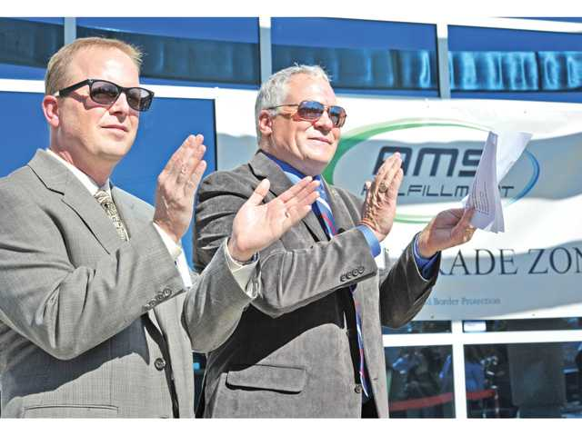 AMS managing partners, President Jay Catlin, left, and CEO Ken Wiseman clap at a ceremony introducing their foreign trade zone status at AMS offices in Castaic on Thursday.