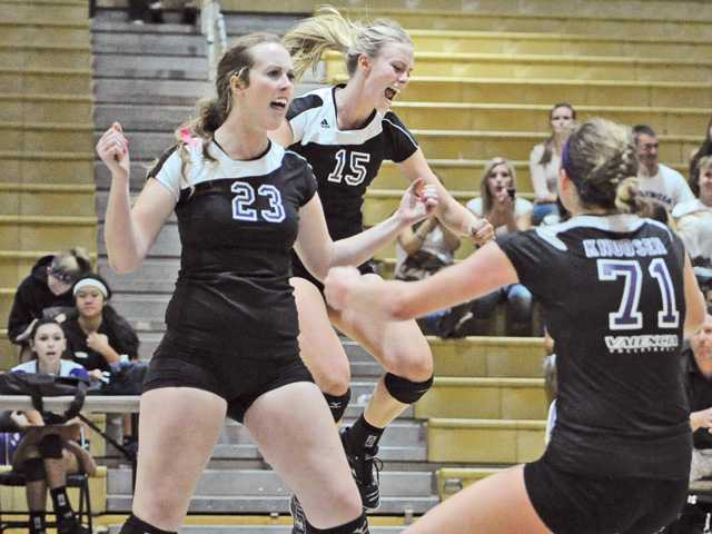 Valencia's Hayley Knapp (23), Kellie Kleszcz (15) and Lindsey Knudsen (71) celebrate a point Thursday at Valencia High.