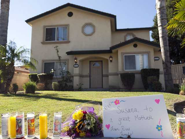Flowers and votive candles are seen outside the home of the owners of a family-owned business, United States Fire Protection Services, in Downey on Thursday.