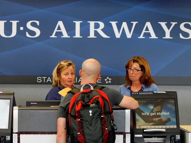 US Airways employees assist a customer at a ticket counter at the Charlotte/Douglas International airport in Charlotte, N.C. Sept. 27, 2012. Some airlines are offering travelers Sandy storm options.