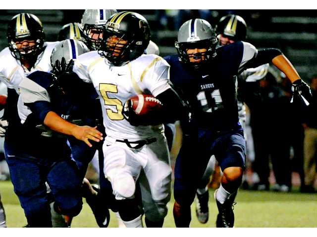 Saugus linebackers Miguel Sanchez, left, and Steven Kwak (11) try to make a stop on Golden Valley running back Terence Tamura on Friday night at College of the Canyons.