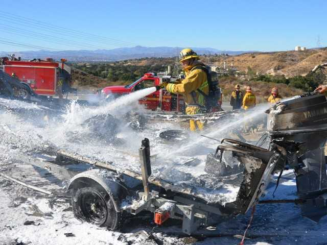 Firefighters cool off the ashes following a boat fire on the side of the Highway 14 freeway in Newhall. Photo by Rick McClure