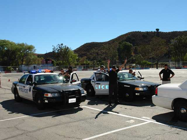 Santa Monica Police Department emergency vehicles operator course instructor Joe Cortez, right, oversees a felony stop exercise at the Saugus Speedway on Thursday.