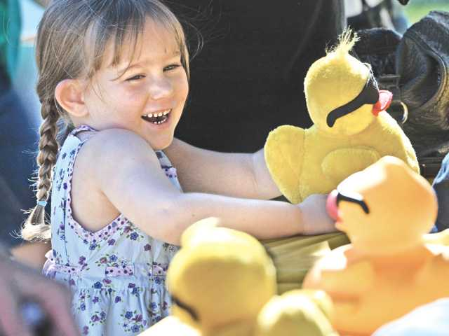 Zoe Wells, 4, picks out a stuffed ducky as her mom adopts a racing ducky at the 10th annual Rubber Ducky Festival at Bridgeport Park in Valencia on Saturday. Signal photo by Dan Watson.