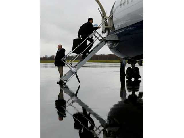 Republican presidential candidate and former Massachusetts Gov. Mitt Romney boards his campaign plane in Akron-Canton Regional Airport, North Canton, Ohio, on Saturday as he travels to Pensacola, Fla., for campaign events.