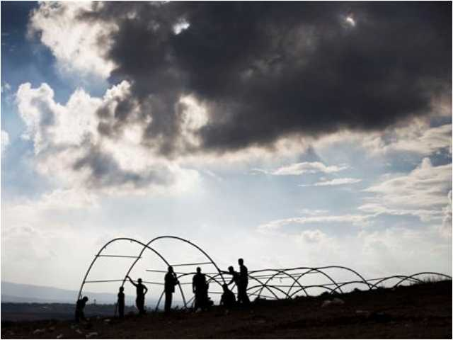 Syrian displaced men build a tent in a refugee camp near Atma, Idlib province, Syria, on Friday, Oct. 26, 2012. A powerful car bomb exploded in Damascus and scattered fighting broke out in several areas across Syria Friday, quickly dashing any hopes that a shaky holiday cease-fire would hold for four days.