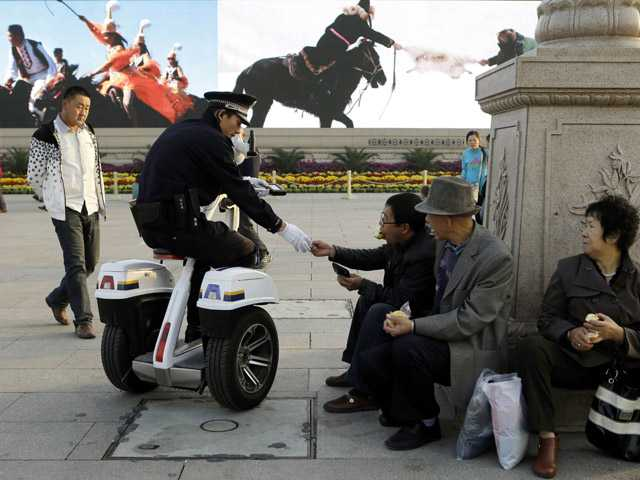 A Chinese police officer checks the identity of Chinese men resting on Tiananmen Square in Beijing on Wednesday.